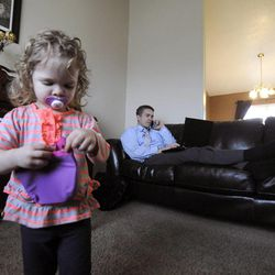 Katelyn, 1, plays with her purse as dad Jeff Griffin checks on his upcoming trip to Las Vegas this weekend in their home in West Jordan on Thursday, Feb. 27, 2014.