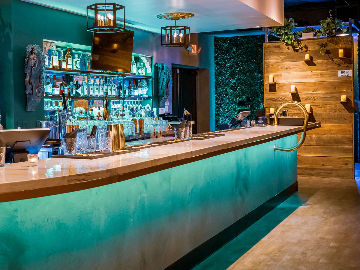 A pretty teal bar with a wood wall on the right.