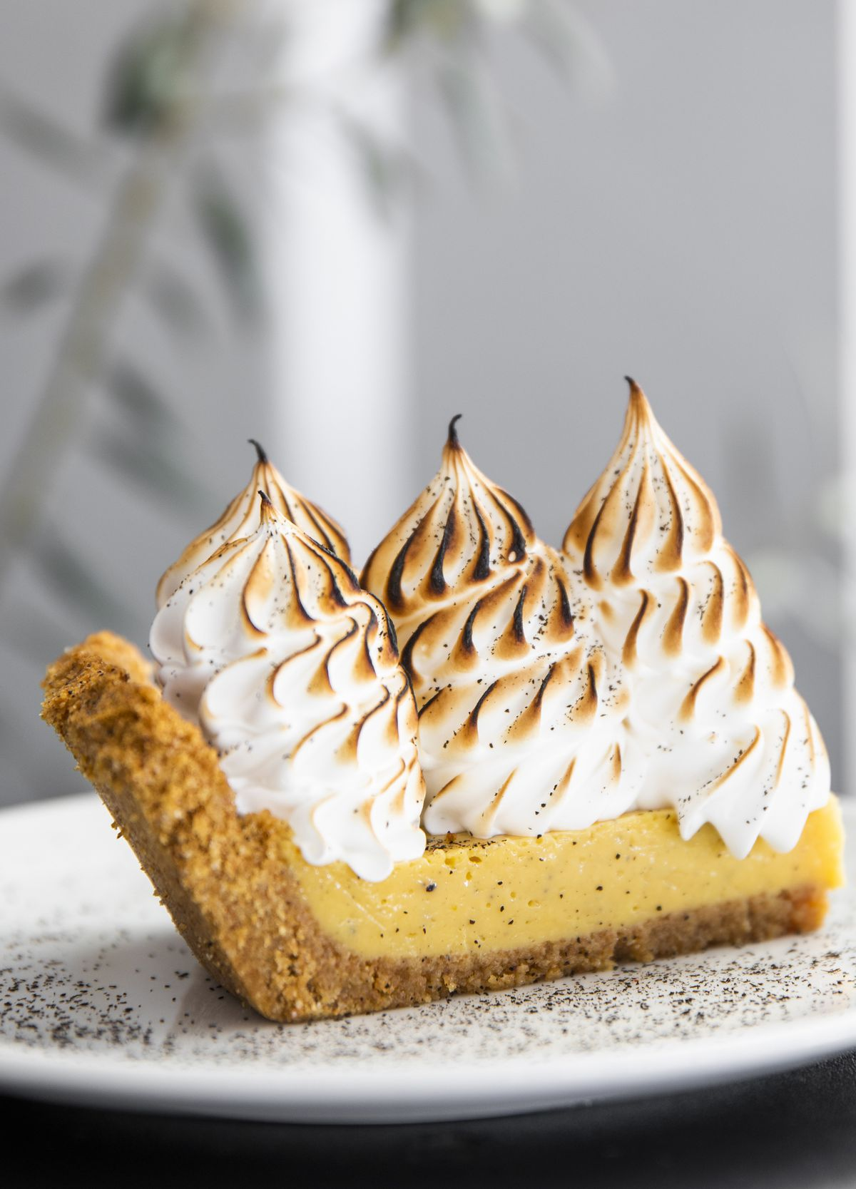 A slice of black lime pie on a white plate with three dollops of toasted meringue