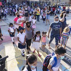 Students and parents wait in line as students return to school on the first day of classes at Alessandro Volta Elementary School.