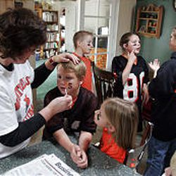 Sue Anderson paints the face of her son Eric, 9, as her daughter Molly, 7, watches. In the background, family friends Dave Fellemth, left, and Jamie Keyes (80) talk with Allyson Anderson as they all prepare for the afternoon's game against Layton Christian in Monticello on Oct. 19. The Anderson family has two sons on the team. The Buckaroos rolled to a 39-0 halftime lead but added only three points in the second half.
