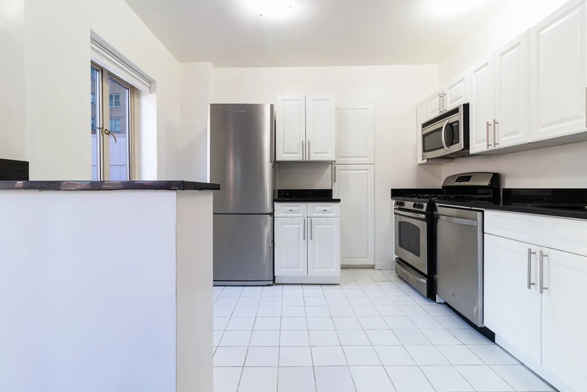 A kitchen with white cabinetry, a window, and white tile floors.
