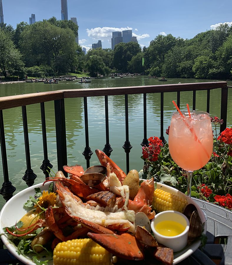 A coral colored cocktail sits on a table with a lobster, corn and salad meal overlooking the water in central park