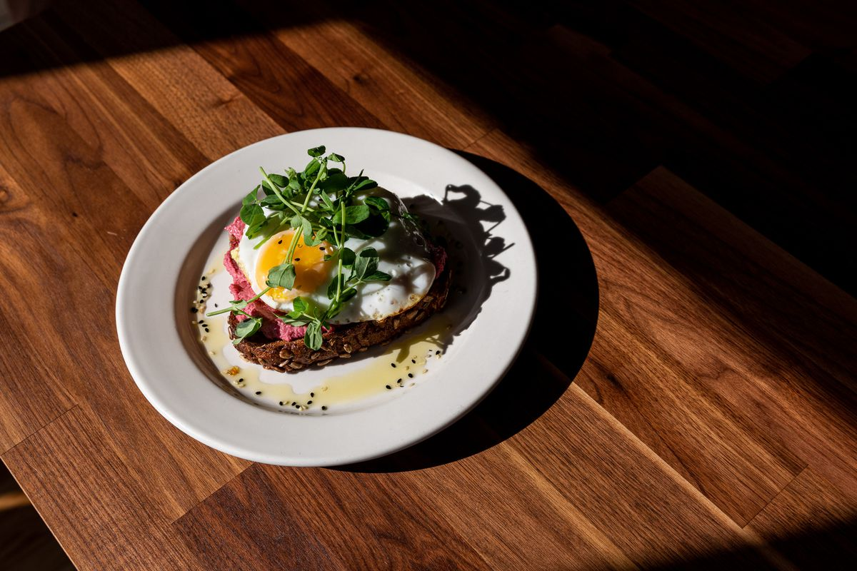 The avocado toast with beet hummus and an egg on top sitting on a brown wood table.