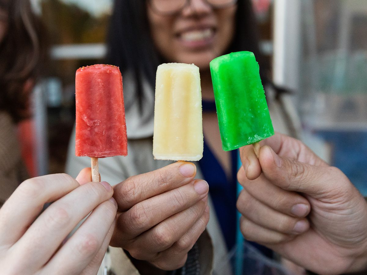 Three people holding up red, yellow and green colorful fruit popsicles