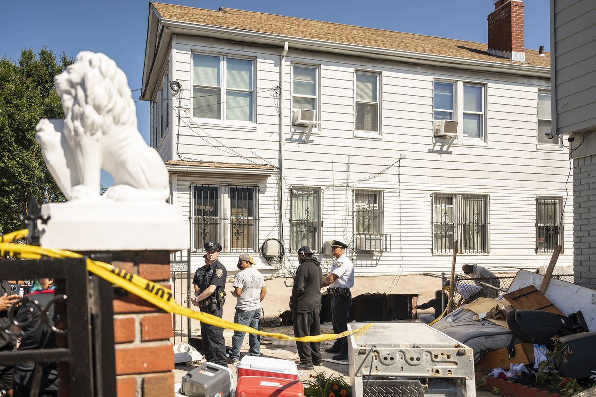 NYPD officers stand at the driveway of a Hollis, Queens, homes where two people died during Wednesday night's flooding, Sept. 2, 2021.