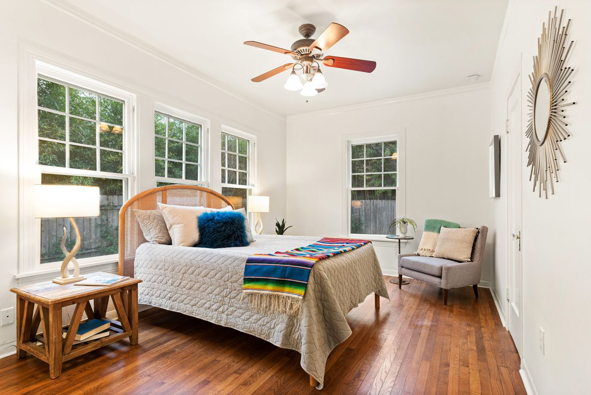A bedroom with wood floors. It has three double-hung windows with a double bed with a wicker frame in front on one wall. There are wooden nightstands with matching curvy lamps with round shades on each side. There's a single window on another wall and an armchair with a tall round side table in the corner.