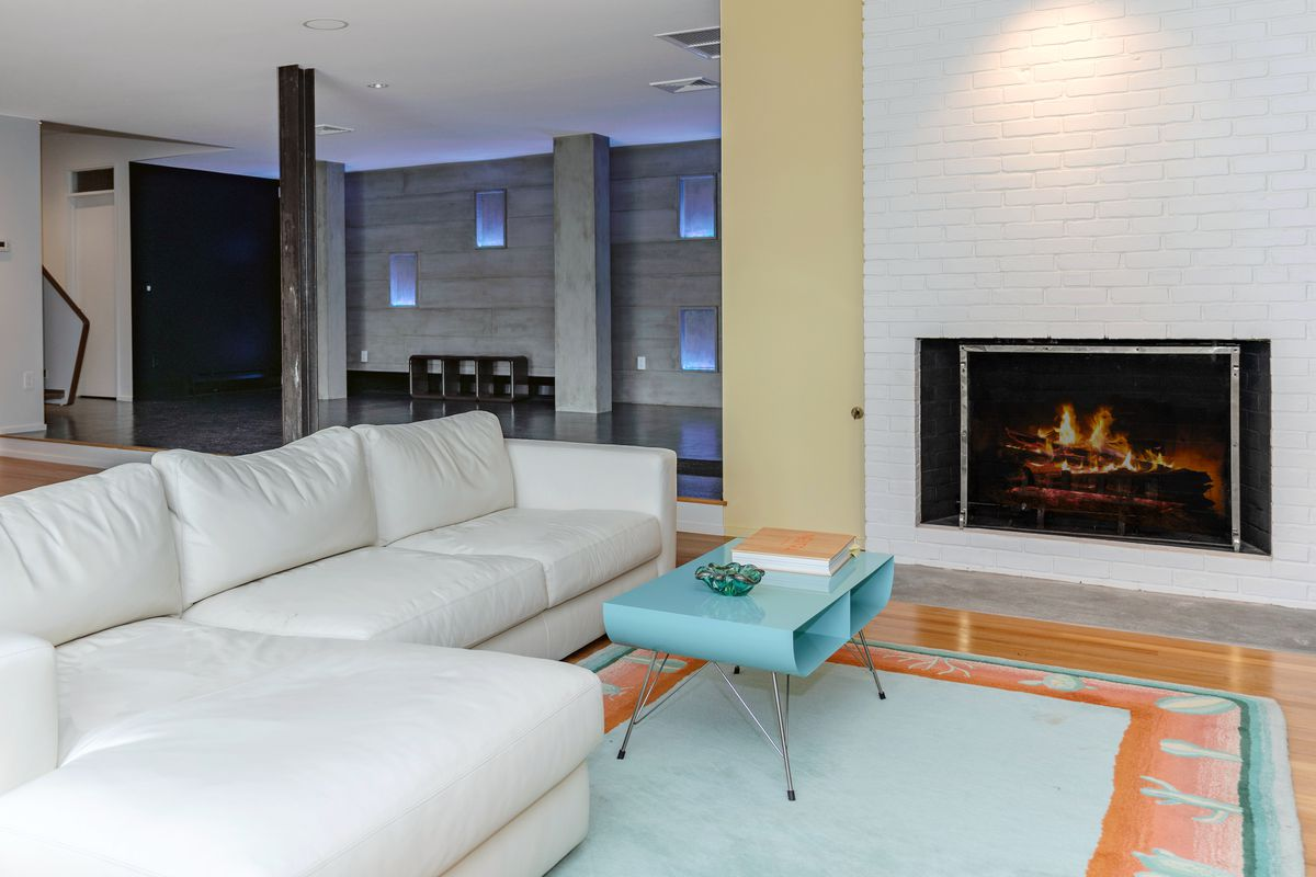 A lower level lounge room with white couch facing a white brick fireplace.