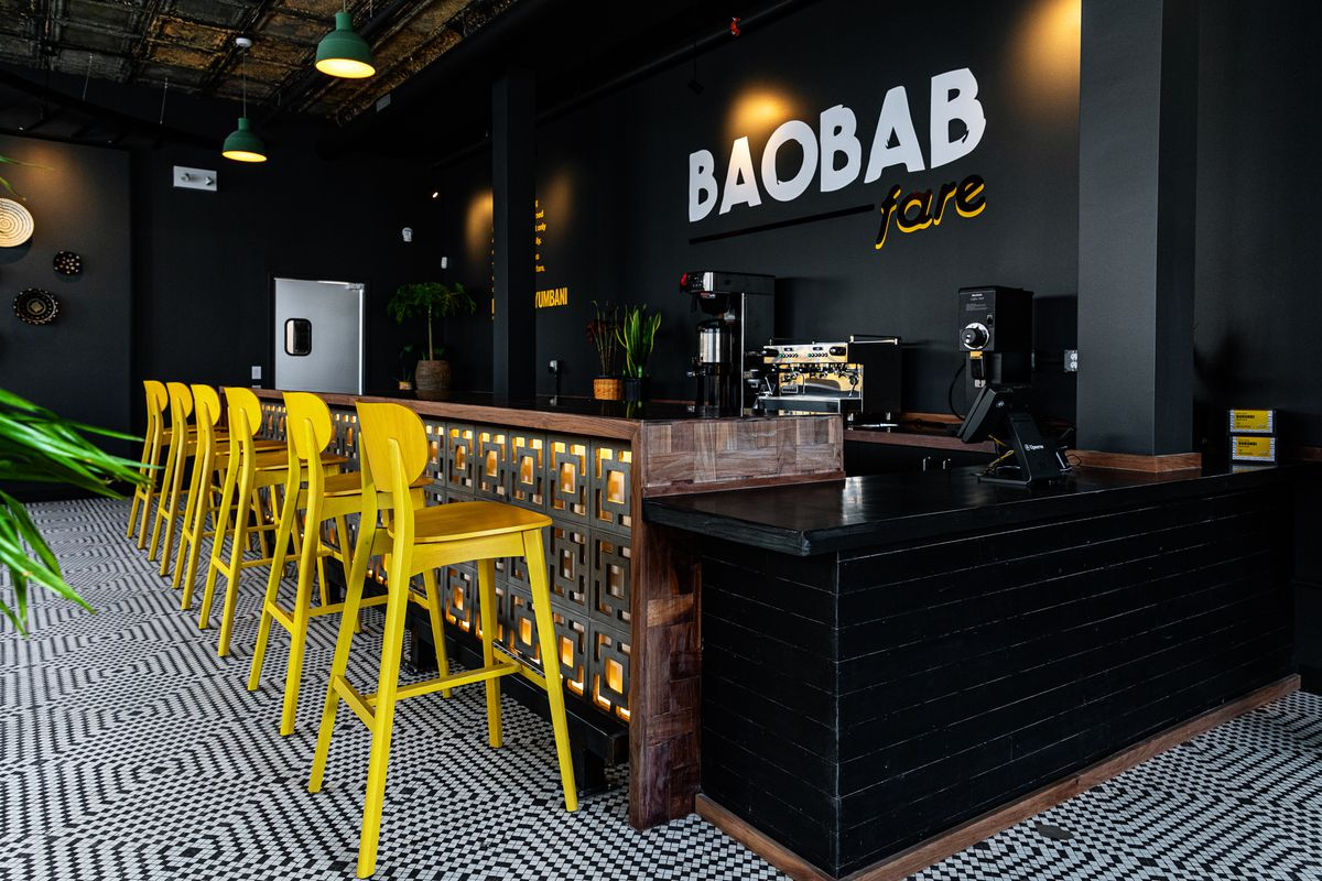 A shot looking down the bar at Baobab Fare with six bright yellow bar stools set atop a blue and white tile floor
