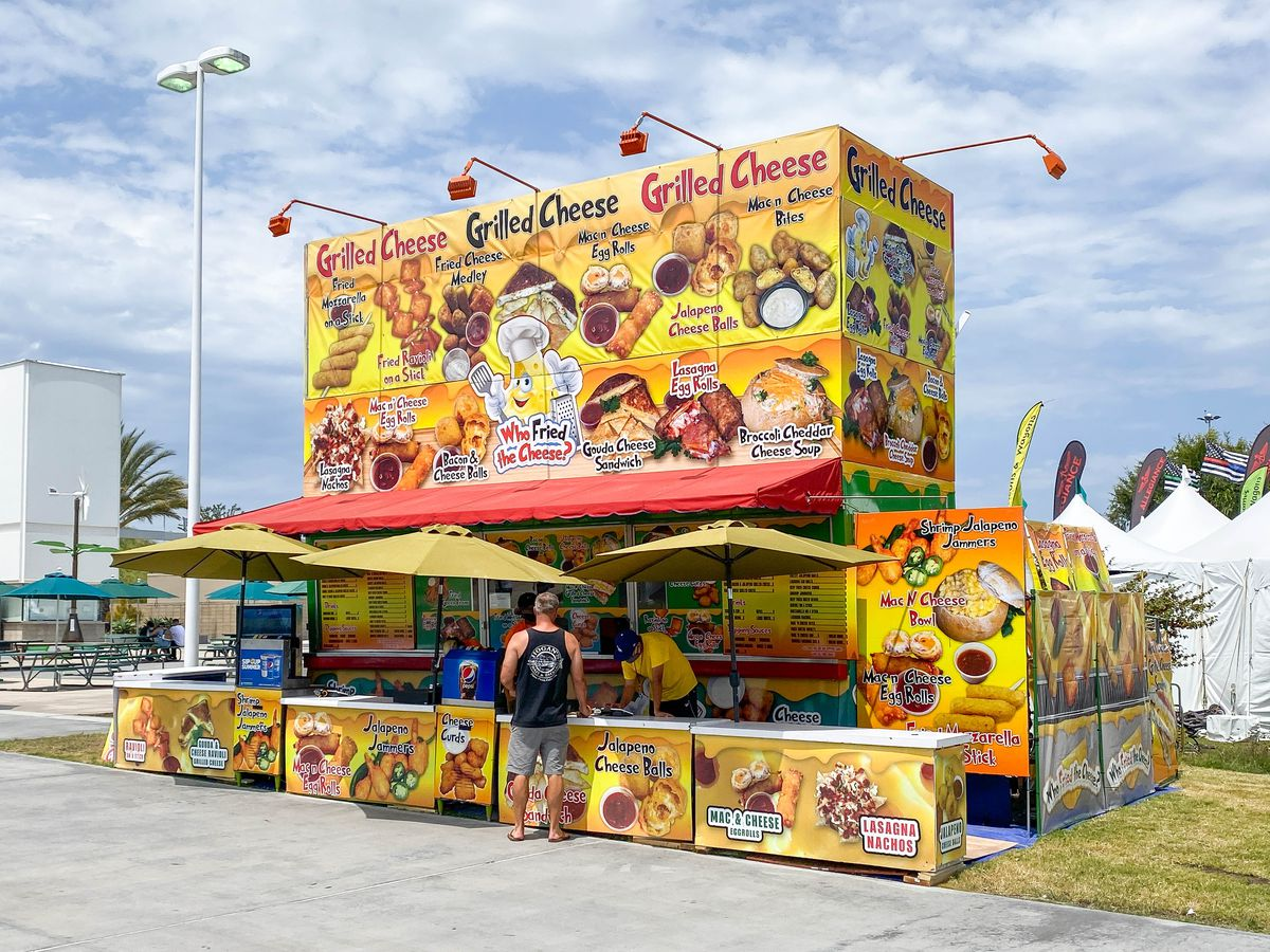 A tilted shot of a yellow stand at a county fair that sells cheese.