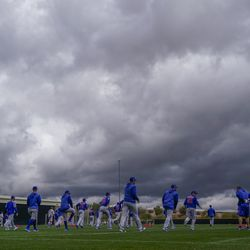 Chicago Cubs players stretch under a cloudy sky during a spring training baseball workout Monday, Feb. 18, 2019, in Mesa, Ariz.   Morry Gash/Associated Press