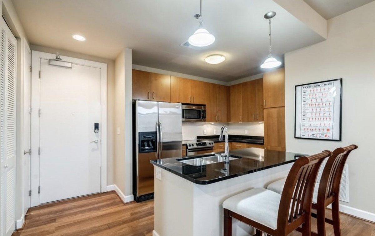 Kitchen with wood cabinets, stainless appliances, and black countertops.