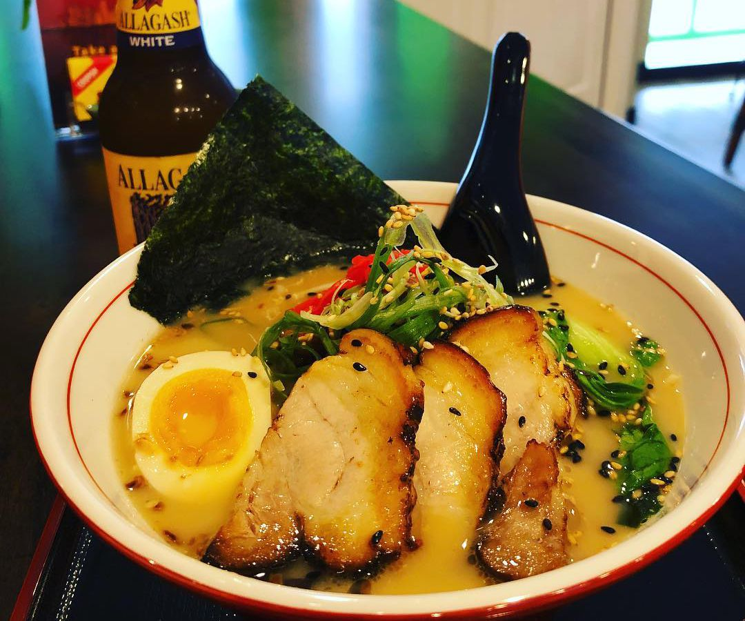 a bowl of ramen with pork slices, a boiled egg, a sheet of seaweed and a spoon