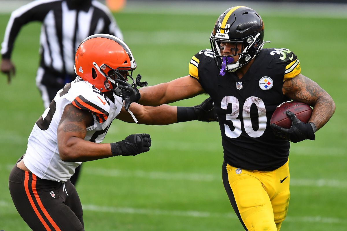 James Conner #30 of the Pittsburgh Steelers stiff arms Malcolm Smith #56 of the Cleveland Browns during their NFL game at Heinz Field on October 18, 2020 in Pittsburgh, Pennsylvania.