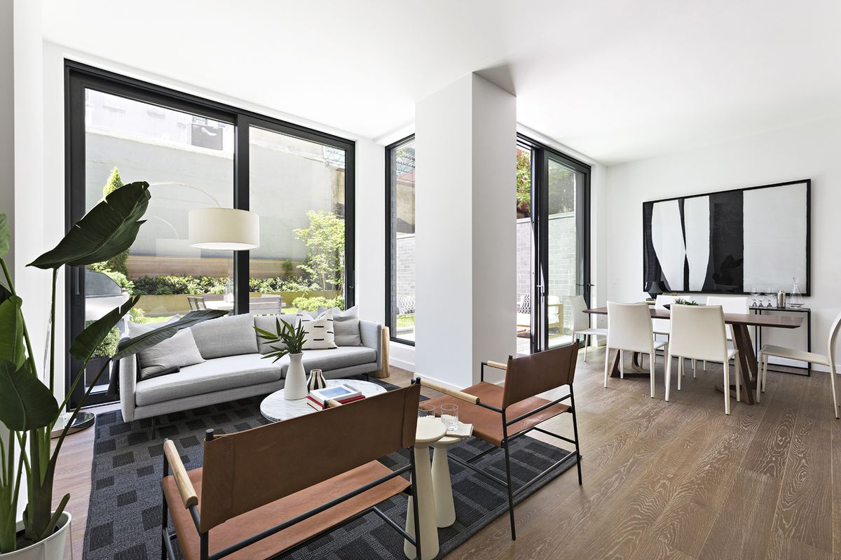 A living area with hardwood floors, a black rug, a grey couch, a planter, and a large glass door that leads to a terrace.