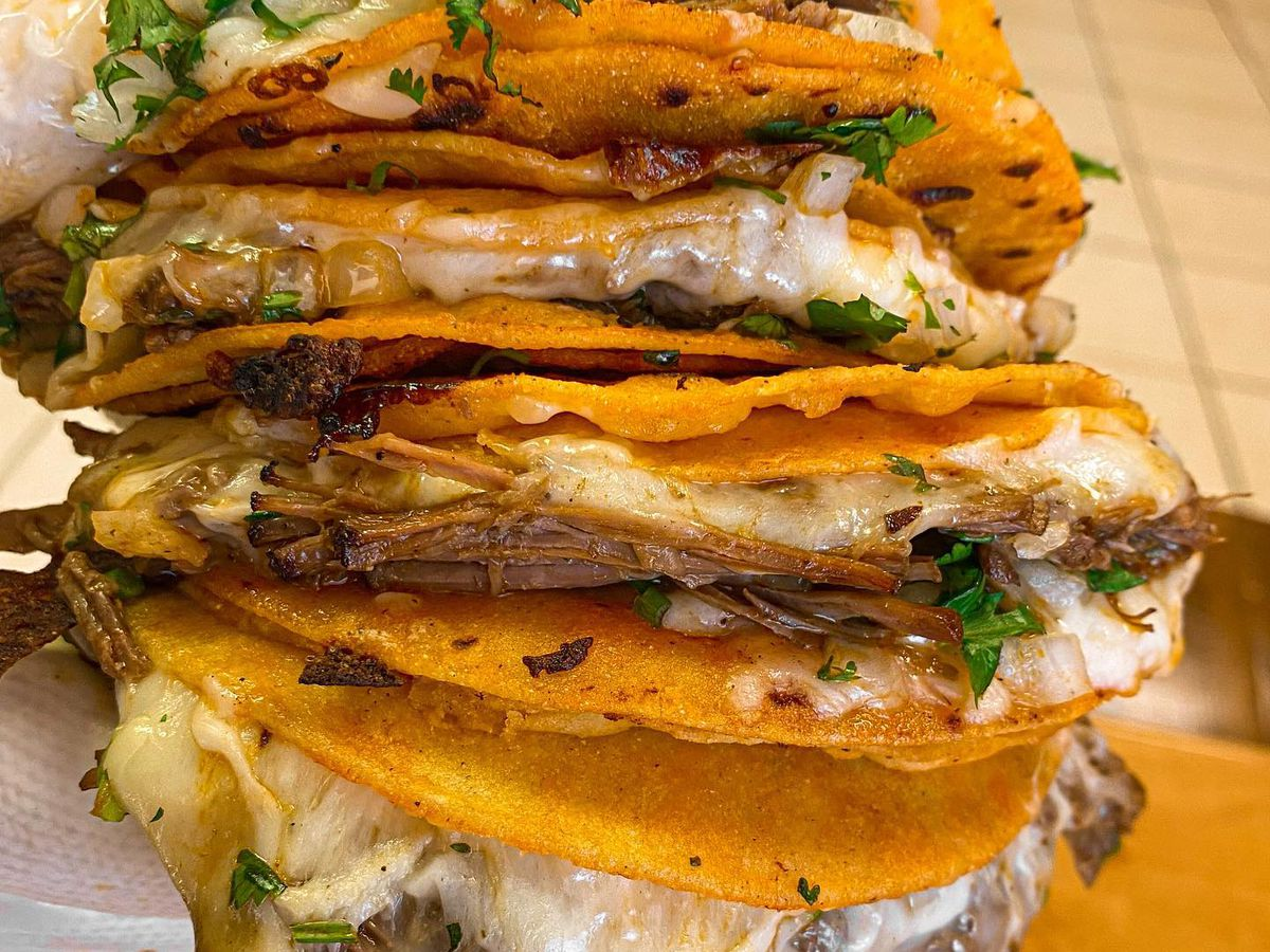 A stack of four crispy tacos with cheese and meat stew.