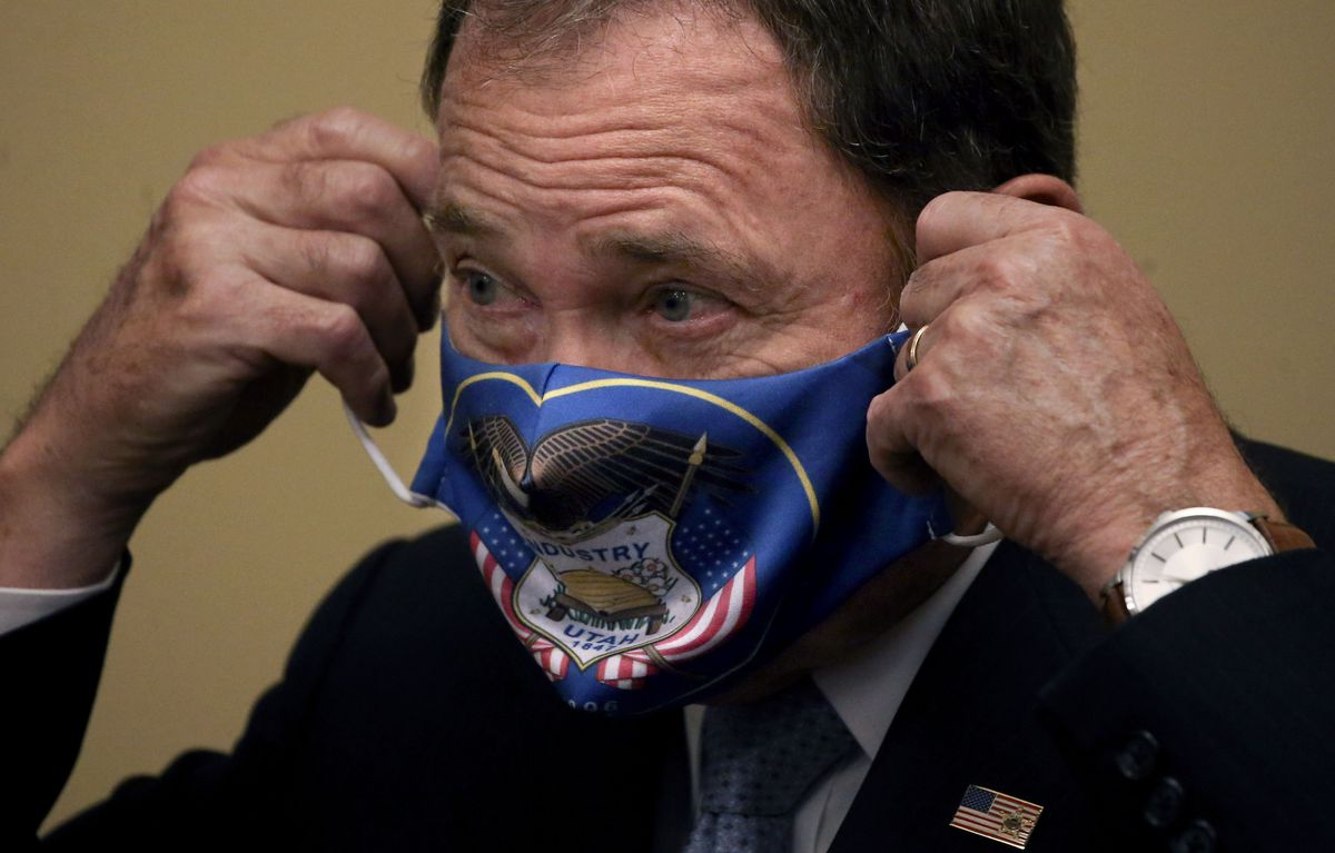 Gov. Gary Herbert puts on a face mask after speaking at a press conference at the Capitol in Salt Lake City on Thursday, July 9, 2020. The governor announced that he is expanding face mask requirements to all schools, but he did not make a general requirement statewide.