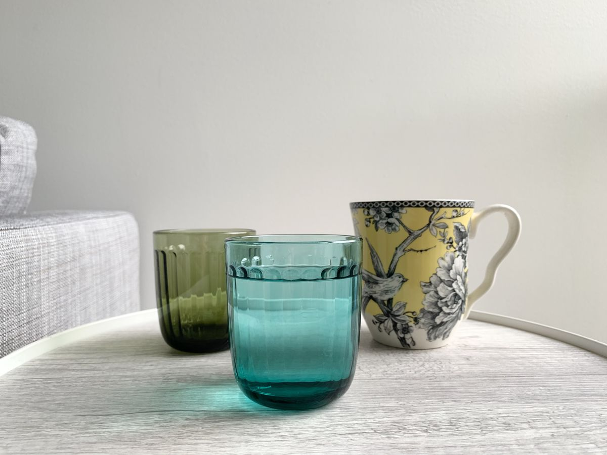 Small green and blue glass cup and a yellow and black mug.