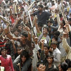 Pakistani Christians wave bamboo sticks as they chant slogans during a rally in Lahore, Pakistan on Wednesday, Aug. 5, 2009. Pakistani Christians staged the mass protest against a Muslim mob's brutal killings of eight of their community members, with some smashing up buses to vent their frustration.