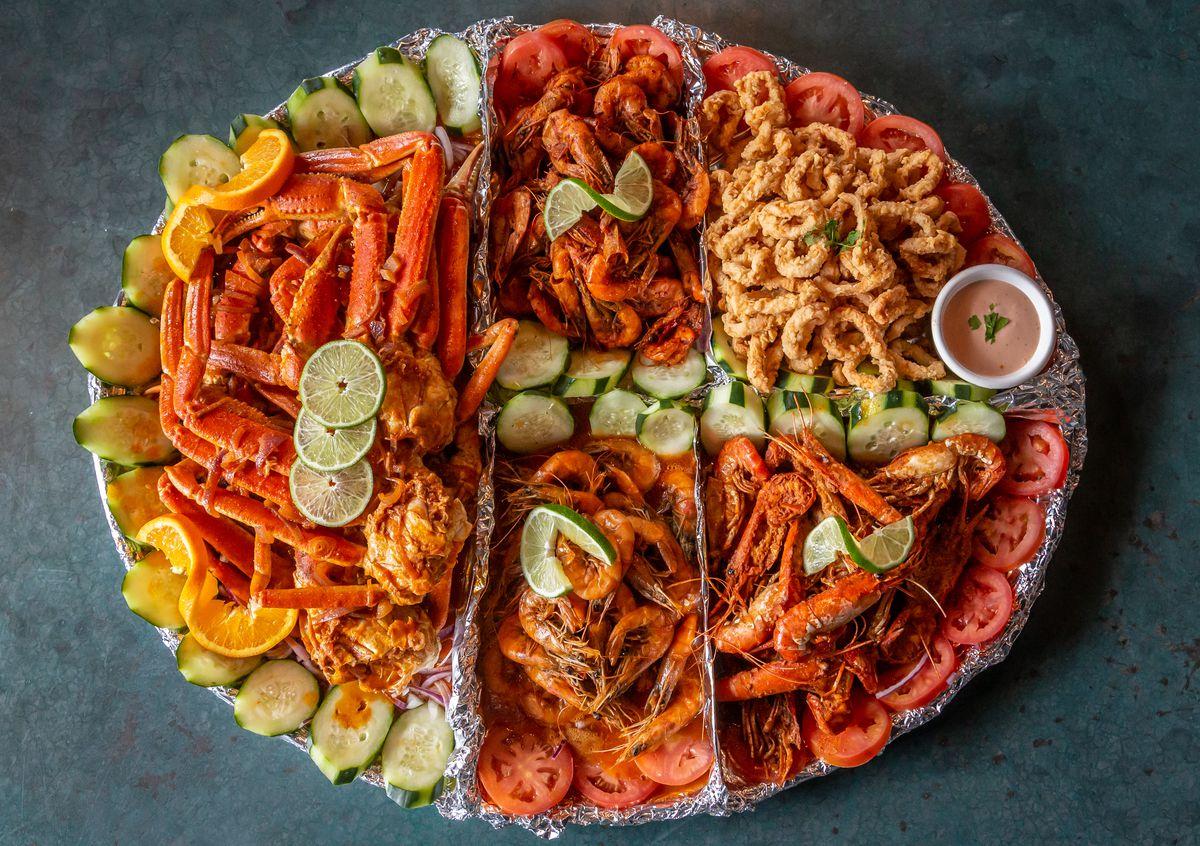 The charola platter with crab legs, langoustines, shrimp, clams, and fried fish at Mariscos La Riviera Nayarit