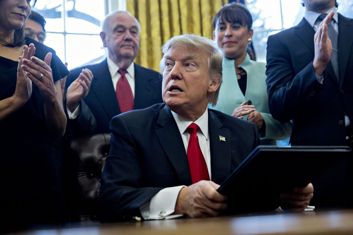 WASHINGTON, DC - JANUARY 30: (AFP OUT) U.S. President Donald Trump pauses after signing an executive order in the Oval Office of the White House surrounded by small business leadersJanuary 30, 2017 in Washington, DC. Trump said he will 'dramatically' redu