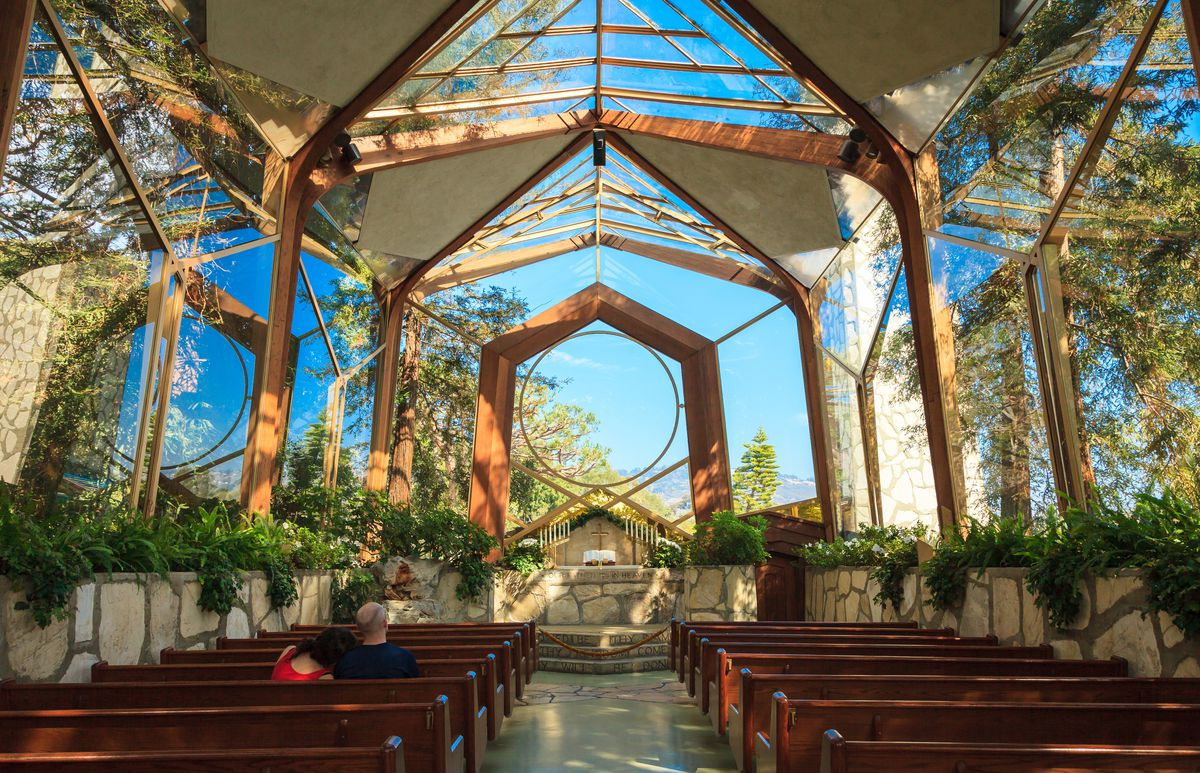The interior of the Wayfarers Chapel in Los Angeles. The walls and ceiling are glass. There are wooden support beams and plants lining the walls of the church.