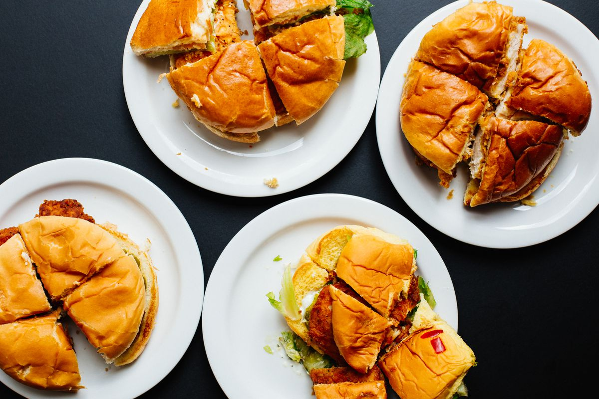 An overhead shot of four chicken sandwiches, cut into quarters and arranged on plates.