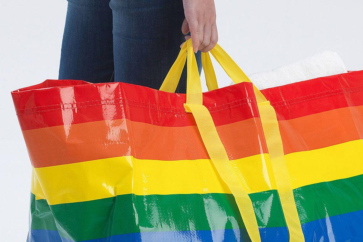 Man holding rainbow plastic bag