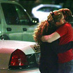 Two people comfort one another outside Trolley Square Monday night after police say a gunman entered the mall and began randomly shooting patrons.