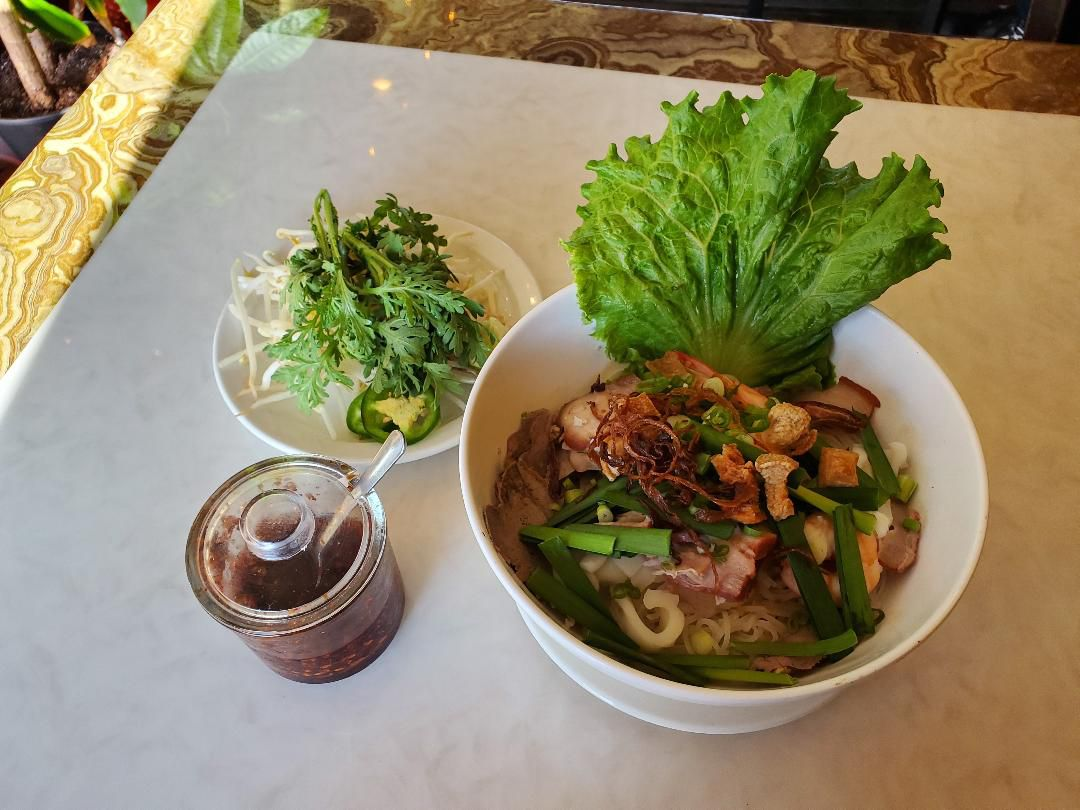 A bowl of soup, with a giant leaf of lettuce sticking out of brown broth, and sauce and salad on the side.