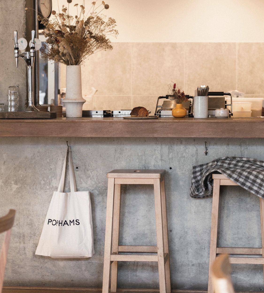London's best restaurant merch includes this Pophams tote bag hanging from a bar