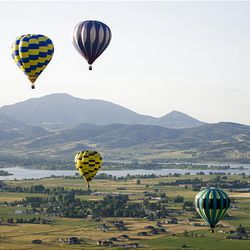 """Balloons hover over Weber County on Friday during the 15th annual Ogden Valley Balloon Festival in Eden, which runs through Sunday. Each evening at the festival field there will be a live concert with BBQ dinner offered for purchase. The popular """"Balloon Glow"""" will take place Saturday evening at dusk"""