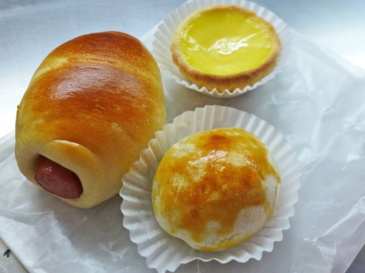 Three pastries dramatically lit, including a yellow custard pie and roll with hot dog peeping out.