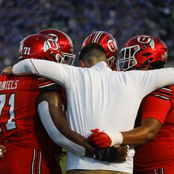 Utah players huddle with a coach ahead of an NCAA college football game against BYU at LaVell Edwards Stadium in Provo on Saturday, Sept. 11, 2021.