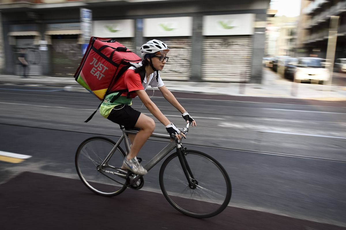A Just Eat courier rides during his work delivering food
