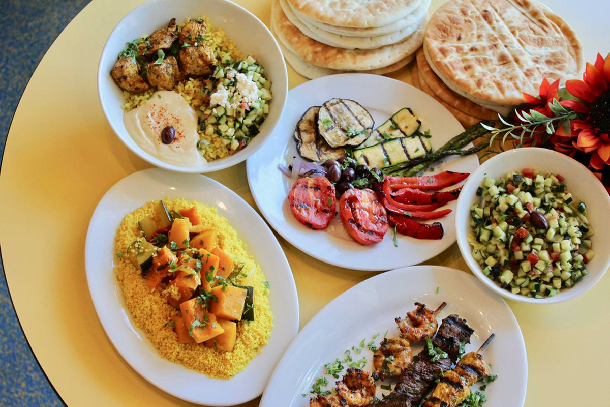 A table filled with pita, bowls, skewers, salad and sides from the casual Mediterranean menu at Crazy Pita.