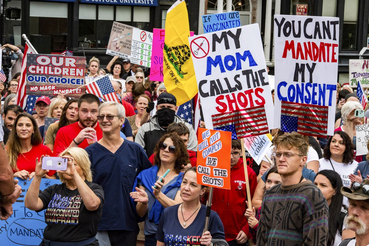 """Demonstrators gather outside the Massachusetts State House in Boston to protest Covid-19 vaccination and mask mandates with signs reading, """"My mom calls the shots,"""" and """"You can't mandate my consent."""""""