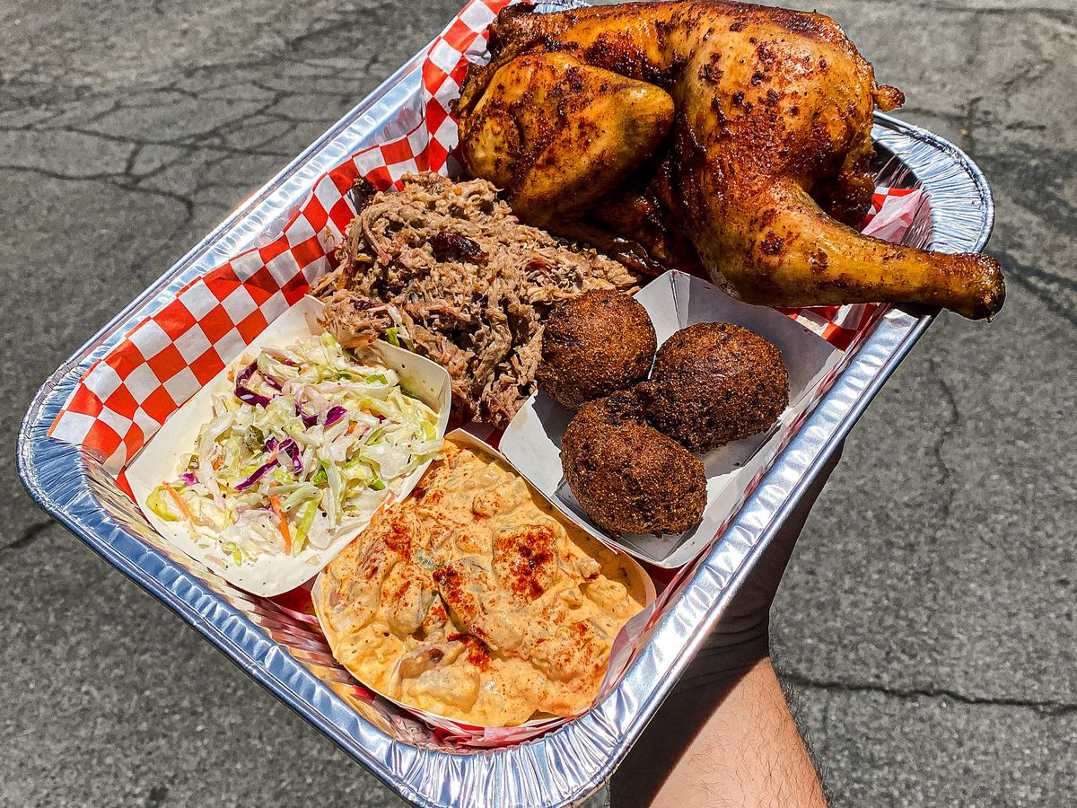 A tray of barbecue, including a smoked half chicken, in a hand in front of a sidewalk.
