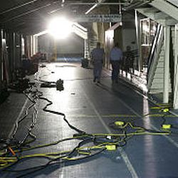 Temporary lights illuminate the indoor track while fans blow to help dry out the water and musty smell. Damage to the building has not yet been fully assessed.