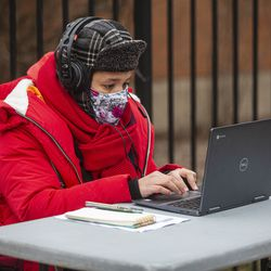 Elementary teacher Melissa Georgiou sits outside of Suder Elementary to teach a virtual class in solidarity with pre-K educators forced back into the building at 2022 W Washington Blvd in West Town, Monday, Jan. 11, 2021.