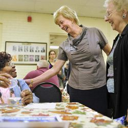In this Tuesday, Sept. 18, 2012 photo, Republican candidate for U.S. Senate Linda McMahon talks with Cluster Hollie, left, as Ellen Manke, right, watches, during a visit to the Naugatuck Senior Center in Naugatuck, Conn. Wealthy former pro wrestling executive McMahon is shifting her image from groin-kicking CEO to grandmother in her second bid for a Senate seat from Connecticut. Polls show the strategy seems to be working against three-term Democratic congressman Chris Murphy.