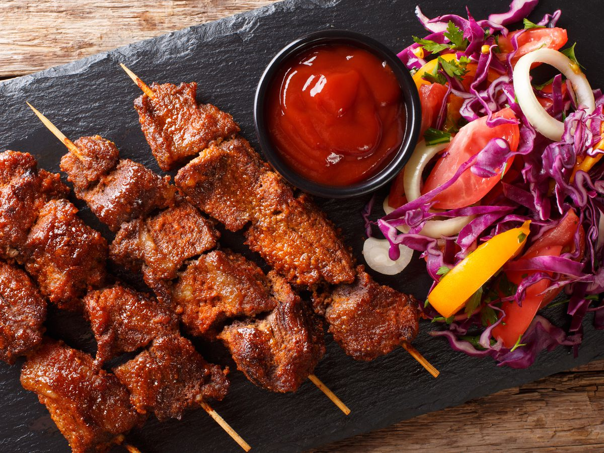 A row of beef skewers on a slate plate, with a side salad and a dipping sauce