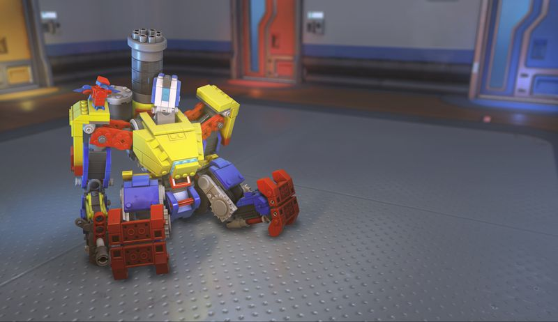 Bastion sits down in his new brightly colored, Lego-inspired Brick Bastion skin in a screenshot from Overwatch