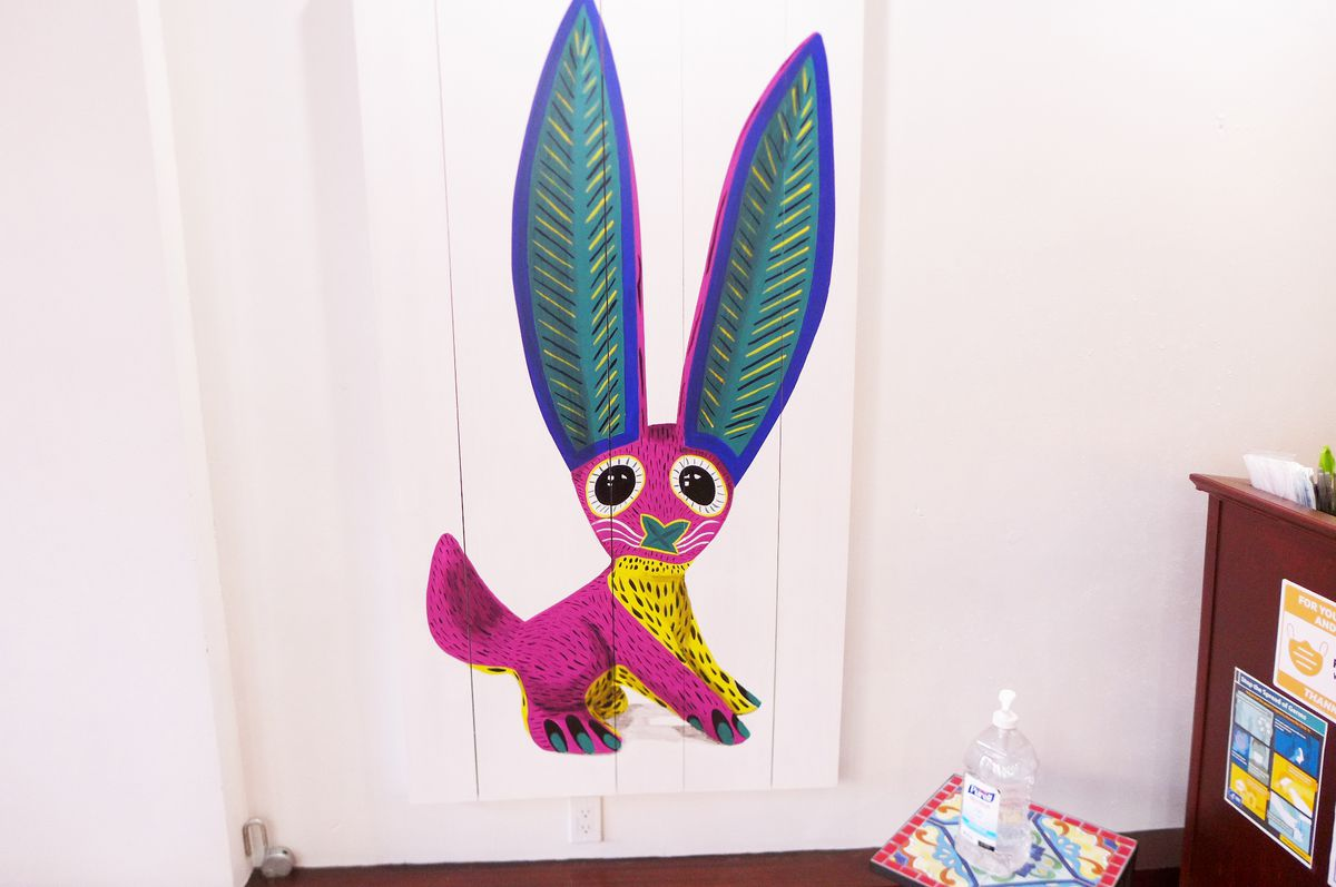 A pink animal with big green ears painted on the wall.