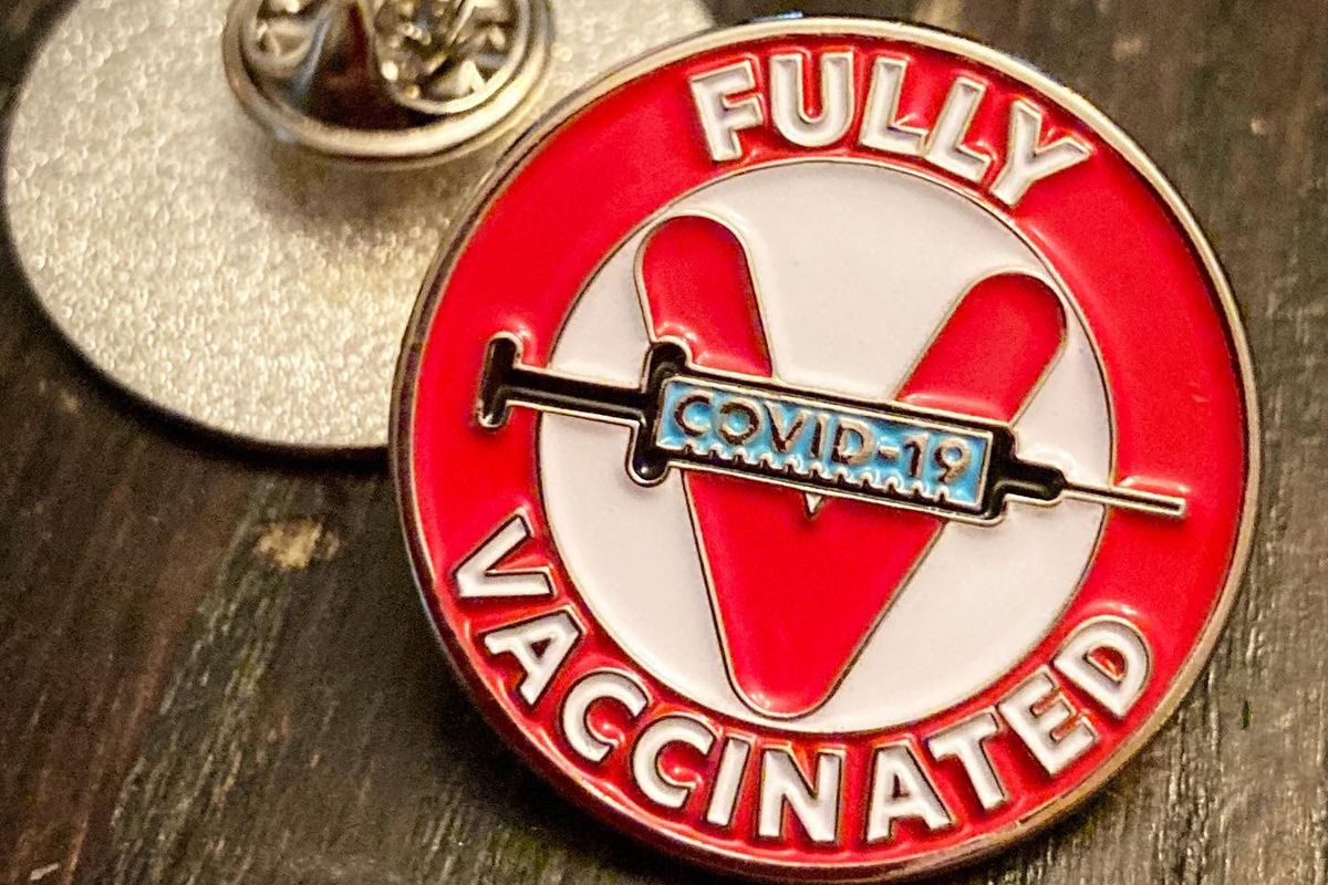 """A metal pin that says """"Fully vaccinated"""" and has a syringe that reads """"Covid-19."""""""