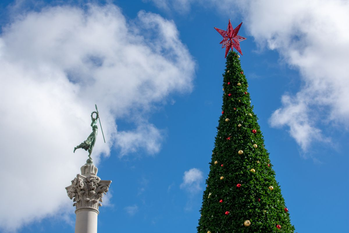 The top of the Macy's Christmas Tree in Union Square, next to the Goddess of Victory atop the pillar nearby.