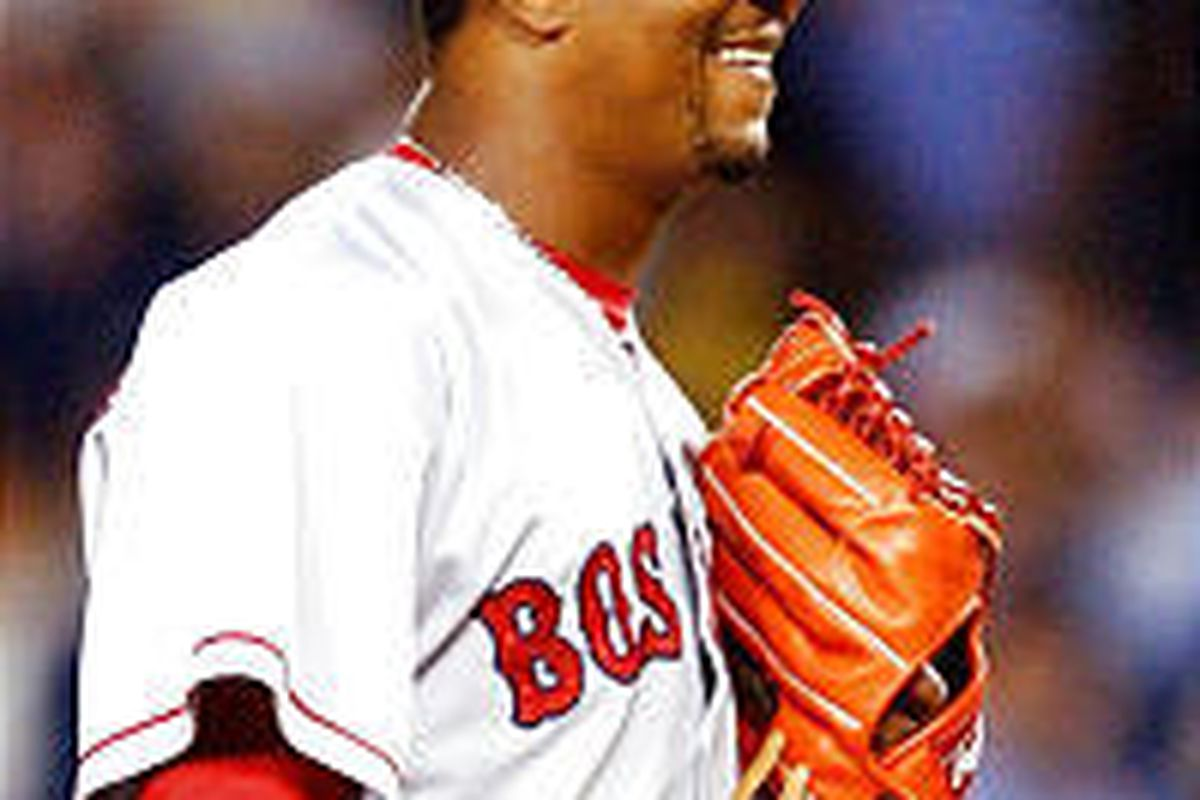 Boston's Pedro Martinez grins after teammate Manny Ramirez caught a long fly ball Friday.