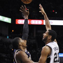 San Antonio Spurs forward Tim Duncan, right, shoots over Utah Jazz forward Derrick Favors during the second half of an NBA basketball game, Wednesday, Jan. 15, 2014, in San Antonio. San Antonio won 109-105.(AP Photo/Darren Abate)