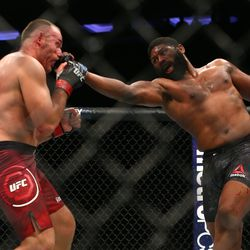 Heavyweight Curtis Blaydes throws a punch at Aleksei Oleinik in the centre of the cage.