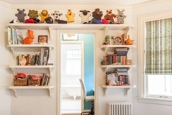 A room with shelves on both sides and above a doorway. The shelves are full of books, toys, and objects. The walls are white.